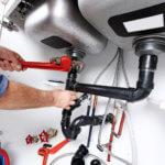 plumber fixing plumbing under sink