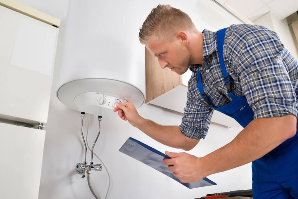 Worker Adjusting Temperature Of Water Heater