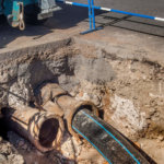 New plastic sewer pipe being inserted into a broken cast iron pipe.
