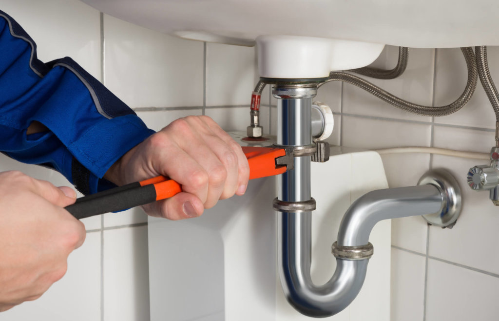 Male Plumber Repairing Apartment Sink In Bathroom