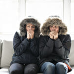 Cold couple on the sofa at home with winter coat