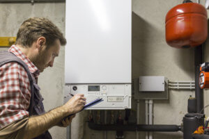 man cleaning and maintaining a boiler